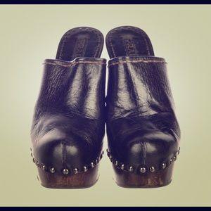 Black leather Prada round-toe platform clogs.